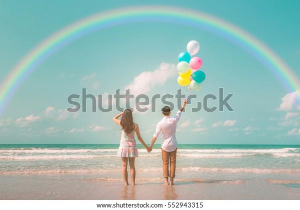 風船と虹のパステル色の色合いを持つ、トレンディのビンテージ服を着た若い幸せな夫婦ヒップスターのポートレート