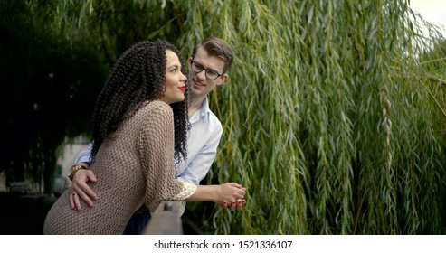 Portrait of a couple-brunette with curly hair, red lips and a guy in glasses. They stand by the willow, leaning on the railing of the bridge, looking into the distance and talking.