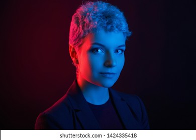 Portrait of a courageous woman with a short haircut in a neon red, blue light. Night life. Clubber, night life concept