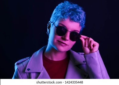 Portrait of a courageous woman with a short haircut in neon pink, blue light in sunglasses and a leather jacket and cap. Night life. Clubber, night life concept
