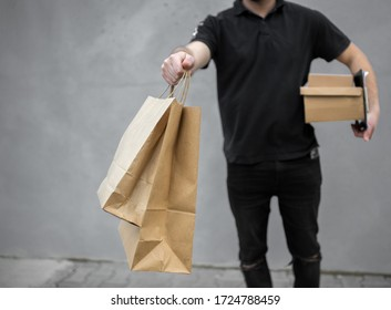 Portrait of courier with order papers and packages with food near grey wall