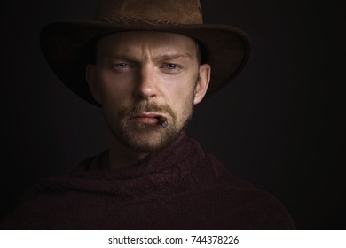 Portrait of cowboy smoking cigar and standing in front of dark background