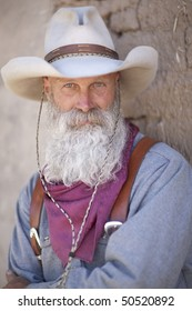 Portrait of a cowboy wearing a tall hat and sporting a long white beard. He is dressed in a heavy work shirt and kerchief. Vertical shot.