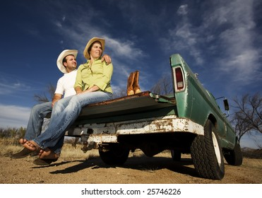Portrait of Cowboy and woman on pickup truck bed