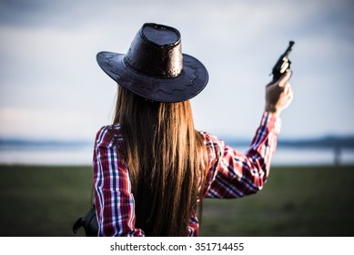 Portrait of a cowgirl in a hat holding gun