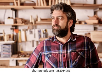 Portrait of a craftsman and owner of an artisan carpentry business in his workshop, looking away from the camera towards the light with a serious and confident expression.