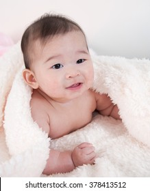 Portrait of a crawling baby on the bed with blanket
