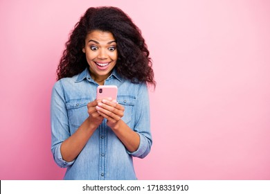 Portrait of crazy addicted afro american girl use smartphone read social media information get like impressed scream wow omg wear denim jeans shirt isolated pink color background
