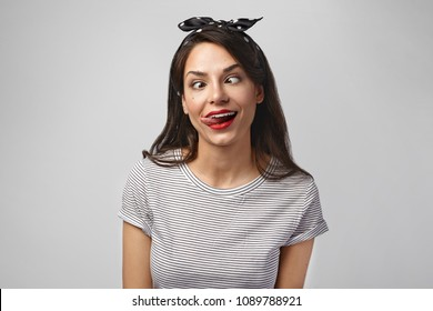 Portrait of crazy beautiful young Caucasian female with dark hair marking goofy face, squinting eyes and sticking out tongue while fooling around, posing in studio. Human facial expressions