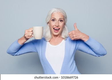 Portrait of crazy coffee lover. Joyful happy excited grandmother grandma is showing thumb-up and big cup of coffee, she is recommending to drink it to be fresh and awake, isolated on gray background