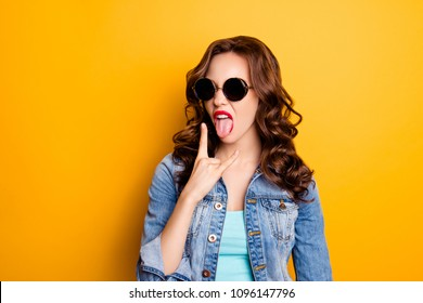 Portrait of crazy cool bitch fashionable girl in summer glasses gesturing tongue out showing rock and roll sign having modern hairdo isolated on yellow background