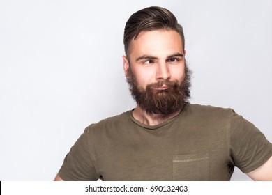 Portrait of crazy cross eyed bearded man with dark green t shirt against light gray background. studio shot.