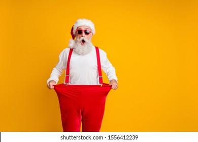 Portrait d'un grand-père à barbe blanche délirant à santa claus qui tient un grand pantalon perdent du poids ventre x mas temps show effet de régime isolé arrière-plan jaune