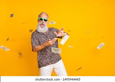 Portrait von verrückt lustigen lustigen alten, langbärtigen Mann Millionär in Brillen Brillen verschwenden Geld werfen Banknoten tragen Leopardenhemd-Shorts einzeln auf gelbem Hintergrund