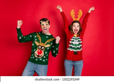 Portrait of crazy funny two family wife husband brown hair celebrate victory raise fists scream yes wear christmas tree design pullover jeans costume spectacles isolated over red color background