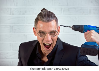 Portrait of crazy funny young man in black suit smiling at camera with a drill holds at his temple. indoor studio shot. Fuck the brain
