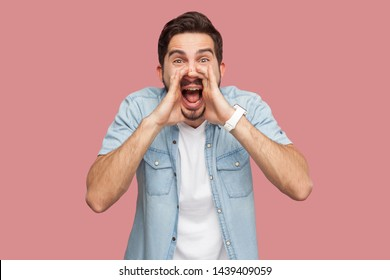 Portrait of crazy handsome bearded young man in blue casual style shirt standing with hand on face, looking at camera and screaming. indoor studio shot, isolated on pink background.