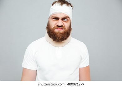 Portrait of crazy injured bearded young man over white background