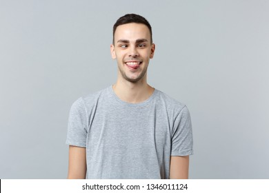 Portrait of crazy loony funny young man in casual clothes with beveled eyes showing tongue isolated on grey wall background in studio. People sincere emotions, lifestyle concept. Mock up copy space