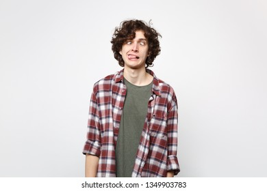 Portrait of crazy loony young man in casual clothes with beveled eyes and showing tongue isolated on white wall background in studio. People sincere emotions, lifestyle concept. Mock up copy space