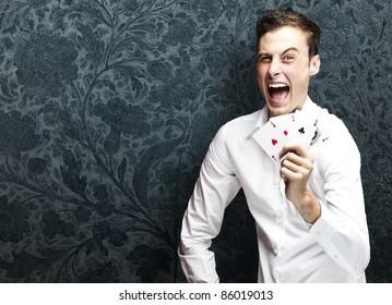 portrait of crazy man showing poker cards against a vintage background