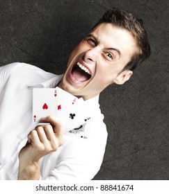 portrait of crazy man showing poker cards against a grunge background