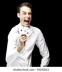 portrait of a crazy man showing poker cards against a black background