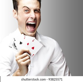 portrait of a crazy man showing poker cards against a grey background