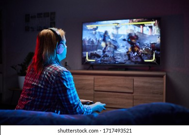 Portrait of crazy playful Gamer , girl enjoying Playing Video Games indoors sitting on the sofa, holding Console Gamepad in hands. Resting At Home, have a great Weekend