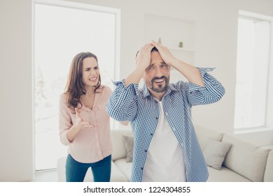 Portrait of crazy sad anxious furious couple having big fight misunderstood showing gesture hands indoors in modern light interior apartments house