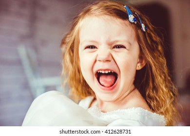 Portrait of the crazy screaming baby girl