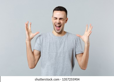 Portrait of crazy screaming young man in casual clothes keeping eyes closed, spreading hands isolated on grey wall background in studio. People sincere emotions, lifestyle concept. Mock up copy space