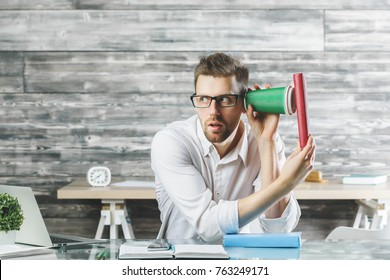 Portrait of crazy suspicious european  man listening to something through take away coffee cup at modern workplace. Weird concept