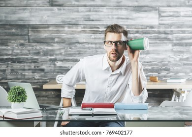 Portrait of crazy suspicious white man listening to something through take away coffee cup at modern workplace. Weird concept