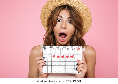 Portrait of a crazy young girl in summer hat holding her menstruation calendar and screaming isolated over pink background
