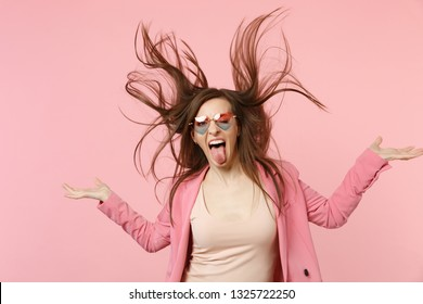 Portrait of crazy young woman in heart glasses showing tongue jumping with flying hair isolated on pastel pink wall background in studio. People sincere emotions lifestyle concept. Mock up copy space