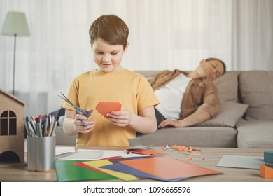 Portrait of creative boy cutting carton by scissors and smiling. His father is sleeping on sofa on background