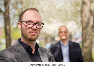 Portrait of a creative business professional, with his aide behind him in the background