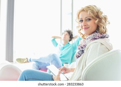 Portrait of creative businesswoman holding digital tablet at lobby with colleague relaxing in background