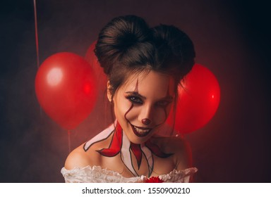 Portrait of a creative image a young woman. Halloween Carnival Party. Beautiful rabid Clown with a frightening grin. Emotions of excitement and bloodthirstiness. Studio balloons, thriller atmosphere.