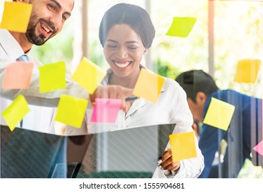 Portrait of creative professionals businessman and woman at office  behind glass wall to use and looking over post it notes to share idea on glass wall.Brainstorming concept. Sticky note on glass wall
