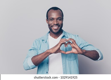 Portrait of creative, romantic, positive, cheerful, confident guy making love symbol, heart figure with fingers, looking at camera, isolated on grey background