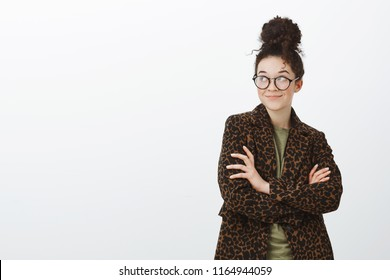 Portrait of creative smart european female coworker in trendy black glasses and leopard coat, holding hands crossed and looking at upper left corner with intrigued pleased smile over gray wall