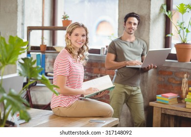Portrait of creative smiling business people discussing in bright office