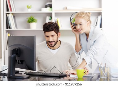 Portrait of creative team working at office and listening music. Young businessman sitting in front of monitor and beautiful businesswoman with headphone standing next to him and share music.