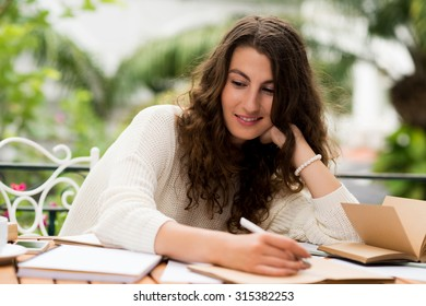 Portrait of creative woman writing down her ideas