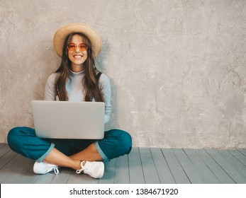 Portrait of creative young smiling woman in sunglasses. Beautiful girl sitting on the floor near gray wall. Model using notebook. Female dressed in hipster clothes and hat