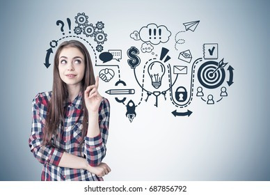 Portrait of a creative young woman wearing a checkered shirt and looking sideways while thinking and pointing upwards. Gray wall background with a business scheme.