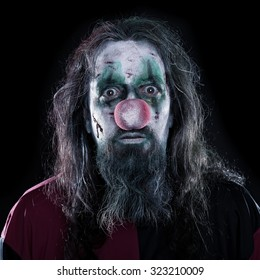 Portrait of a creepy and bloody clown in front of black background, concept Horror or Halloween