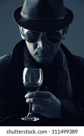 Portrait of criminal mastermind in suit holding glass of wine